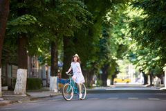 Summer sunny day. Nice girl on bike alone at road. Summer sunny day. A nice girl on a bike alone on the road. Juicy city greens, vintage blue bicycle, a girl Stock Photos