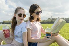 Summer sunny day, two girlfriends teenagers sit on green lawn, drink cocktails, talk, read book, laugh, have fun, golden hour.  stock photography