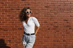 Summer sunny lifestyle fashion portrait of young stylish hipster woman with brunette curly girl stock photo