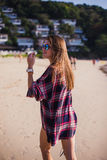 Summer sunny lifestyle fashion portrait of young stylish hipster woman walking on beach,wearing cute trendy outfit Stock Image
