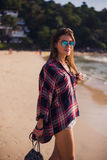 Summer sunny lifestyle fashion portrait of young stylish hipster woman walking on beach,wearing cute trendy outfit Royalty Free Stock Photo