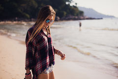 Summer sunny lifestyle fashion portrait of young stylish hipster woman walking on beach,wearing cute trendy outfit Royalty Free Stock Photos