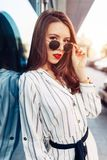 Summer sunny lifestyle fashion portrait of young stylish hipster woman walking on the street, wearing cute trendy outfit royalty free stock photo