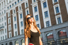 Summer sunny lifestyle fashion portrait of young stylish hipster woman walking on the street, wearing cute trendy outfit Stock Photos
