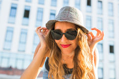 Summer sunny lifestyle fashion portrait of young stylish hipster woman walking on the street, wearing cute trendy outfit Royalty Free Stock Photography