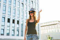 Summer sunny lifestyle fashion portrait of young stylish hipster woman walking on the street, wearing cute trendy outfit Royalty Free Stock Images