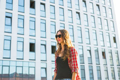 Summer sunny lifestyle fashion portrait of young stylish hipster woman walking on the street, wearing cute trendy outfit Stock Photography