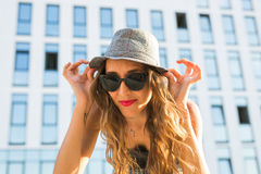 Summer sunny lifestyle fashion portrait of young stylish hipster woman walking on the street, wearing cute trendy outfit Stock Images