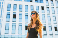 Summer sunny lifestyle fashion portrait of young stylish hipster woman walking on the street, wearing cute trendy outfit Royalty Free Stock Photos