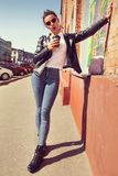 Summer sunny lifestyle fashion portrait of young stylish woman walking on the street, wearing cute trendy outfit, drinking coffee royalty free stock photos