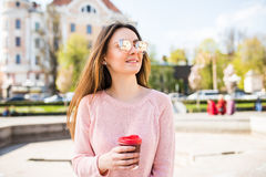 Summer sunny lifestyle fashion portrait of young stylish woman walking on street, wearing cute trendy outfit, drinking hot drink,. Summer lifestyle fashion Stock Images
