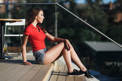 Summer sunny lifestyle fashion portrait of young woman posing in the city.  Stock Photos
