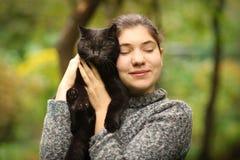 Summer sunny photo of teenager girl hug blackcat stock photography