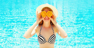 Summer sunny portrait smiling woman holds in hands oranges and hides his eyes Royalty Free Stock Photos