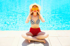 Summer sunny woman holds in hands oranges and hides his eyes on blue water pool Royalty Free Stock Images
