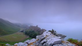 Summer sunrise with a clearing sea mist over the Valley of Rocks, near Lynton on the North Devon coast within the Exmoor National stock photography