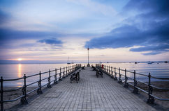 Sunrise at the Banjo Pier at Swanage. Summer sunrise and empty benches ot the Banjo Pier at Swanage in Dorset Stock Photo
