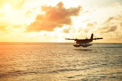 Summer sunrise with seaplane. Landing seaplane on the seashore Royalty Free Stock Image