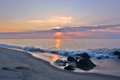 Summer Sunrise at the Shore Over Rock Jetty Stock Photo