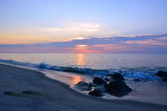 Summer Sunrise at the Shore Over Rock Jetty Royalty Free Stock Photography