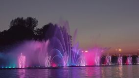 Illuminated fountain and city sunset. Summer sunset in the city. Fountain dynamics and light show stock footage