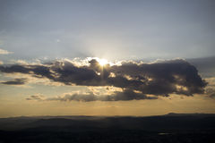 Summer sunset. Clouds over the mountains with the sun peeps through them Royalty Free Stock Photo