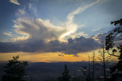 Summer sunset. Clouds over the mountains with the sun peeps through them Stock Photos