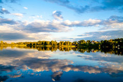 Summer sunset evining sky and clouds reflection in water Royalty Free Stock Images