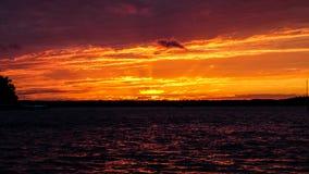 Summer sunset on the horizon across Minnesota lake. Orange red blue colors of summertime vacationland sunset in northern Minnesota Royalty Free Stock Photo
