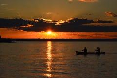 Summer sunset on the horizon across Minnesota lake. Orange red blue colors of summertime vacationland sunset in northern Minnesota Stock Photos