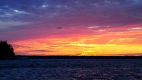 Summer sunset on the horizon across Minnesota lake. Orange red blue colors of summertime vacationland sunset in northern Minnesota Royalty Free Stock Photos