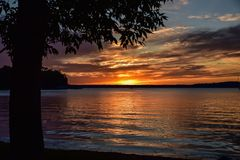 Summer sunset on the horizon across Minnesota lake. Orange yellow colors of summertime vacationland sunset in Minnesota Stock Image