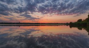Ukrainian summer sunset landscape with cloudy sky reflected by still water stock photo