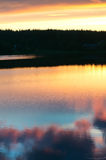 Summer sunset in Lapland. Sunset with relfections from the lake. background forest and houses are almost silhouette stock photo