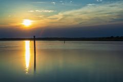 Summer twilight over the lagoon shoreline in Bibiobe, venice. Summer sunset over the lagoon water and shoreline inside Bibione, Venice royalty free stock photography