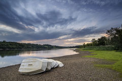 Summer sunset over lake in landscape with leisure boats and equi. Summer sunset over lake in landscape with leisure boats on shore Stock Photos