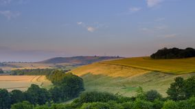 Summer sunset over the South Downs - high resolution stitched panorama of golden hour light falling on Butser Hill from above East royalty free stock image