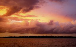 Pink colored cumulus cloud, sunset seascape. Summer sunset with predominately cumulusclouds against a yellow and lilac sky reflected in Australian ocean water royalty free stock image