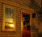 Summer sunset, reflected. Summer sunset reflected in the window and door of a summer cottage Royalty Free Stock Image