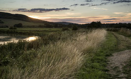 Summer sunset reflected in river in countryside landscape during Royalty Free Stock Photos