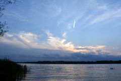 Summer Sunset Reflecting Off Coon Lake, Minnesota. The summer sun is setting behind a growing bank of clouds. The sunset colors reflect off the rippling water as stock photo