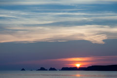 Summer Sunset Silhouette. Summer silhouette of rocky coastline peninsula during colorful orange and yellow sunset with white cloudscape above stock photography