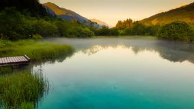 Summer sunset on a small natural clear turquoise blue lake stock image