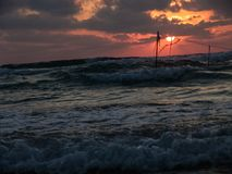 Summer sunset view of a beach under a cloudy sky, with a post in the water and flags flying in the wind, strung, hanging on a rope royalty free stock photos