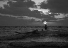 Summer sunset view of a beach under a cloudy sky with a single sup surfer silhouette in black and white royalty free stock photos