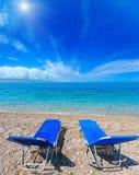 Summer sunshiny Albanian riviera beach. Summer sunshiny beach with sunbeds, white pebble and aquamarine water Albania. Two shots stitch image Stock Photo