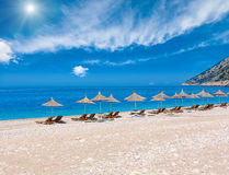 Summer sunshiny Albanian riviera beach. Summer sunshine beach with aquamarine water and clouds in sky, sunbeds and strawy sunshades Albania Royalty Free Stock Photography