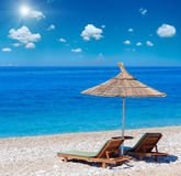 Summer sunshiny beach. Summer morning sunshiny pebbly beach with sunbeds and strawy sunshade Albania. Deep blue sky with same cumulus clouds. Two shots stitch Stock Images