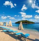 Summer sunshiny Ksamil Beach, Albania. Summer sunshiny sandy Ksamil Beach with sunbeds and sunshades Albania. Two shots stitch high resolution image Stock Photos
