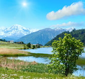 Summer sunshiny mountain landscape with lake Italy. Summer sunshiny mountain landscape with lake Lago di Resia and blue cloudy sky Italy. Two shots stitch image Royalty Free Stock Images